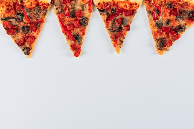 Slices of a pizza flat lay on a bright stucco background