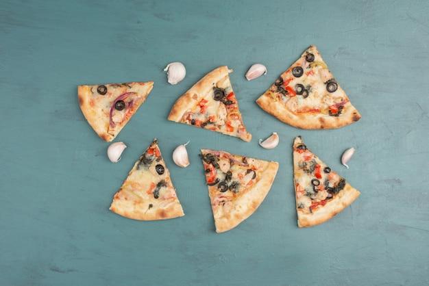 Fette di pizza e pezzi di aglio sulla superficie blu.