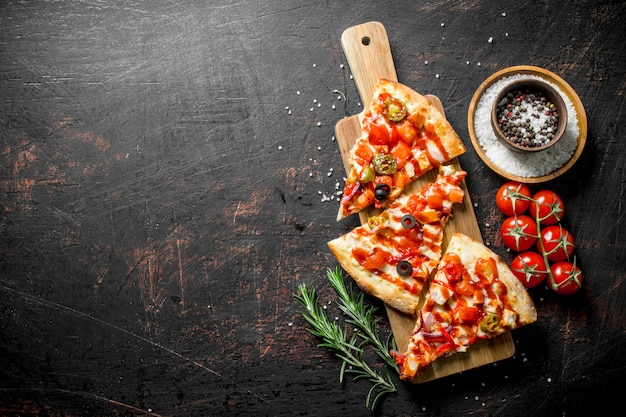 Slices of pizza with spices, tomatoes and rosemary. on dark rustic background