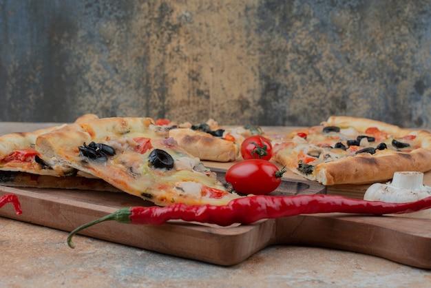 Fette di pizza su tavola di legno con pomodorini e peperoncino.