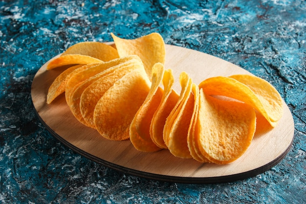 Slices of potato chips on a wooden platform on blue concrete table. top view