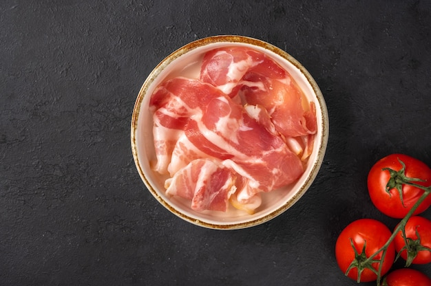 Slices of prosciutto ham in a white ceramic bowl on dark background, next to a branch of cherry