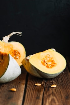 Slices of pumpkin with seeds on wooden background