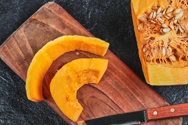 Slices of pumpkin on wooden chopping board with knife.