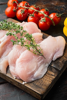 Slices of raw chicken meat fillets, on old dark  wooden table background