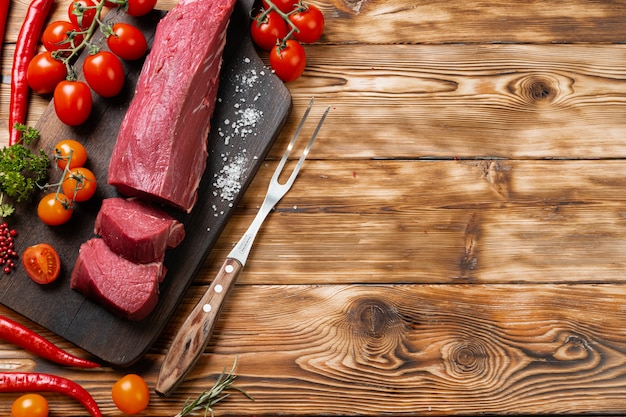 Slices raw meat fillet on wooden board