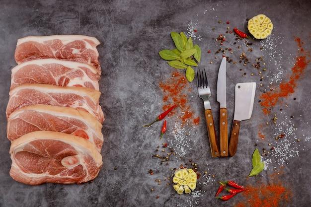 灰色の背景にスパイスとナイフで生のポークチョップ肉をスライスします。上面図。