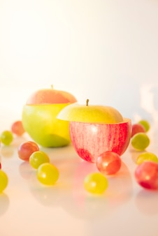 Slices of red and green apple with grapes on white backdrop