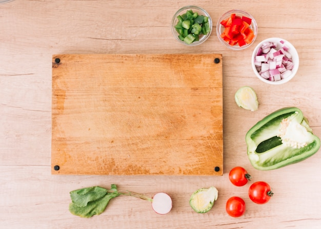 Slices of red; green bell pepper; onion; beet root; cherry tomatoes near the blank chopping board over the wooden desk