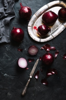 Slices of red onions on a black grunge background