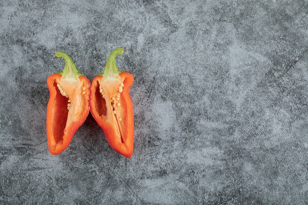 Slices of red pepper on a gray background.