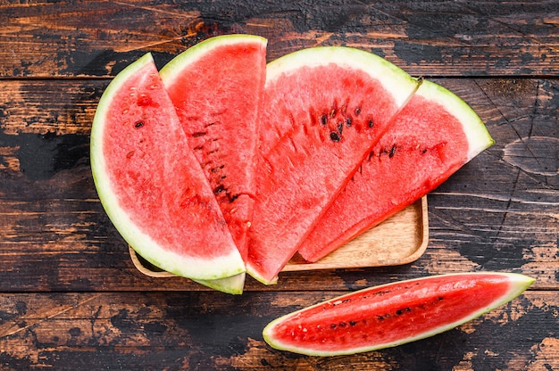 Slices of red striped watermelon. dark wooden background. top view.