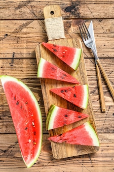 Slices of red striped watermelon. wooden background. top view.