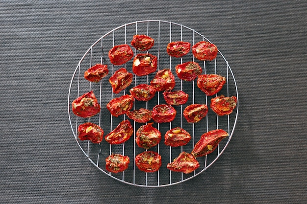 Slices of red tomatoes sun-dried arranged on round metal grid.