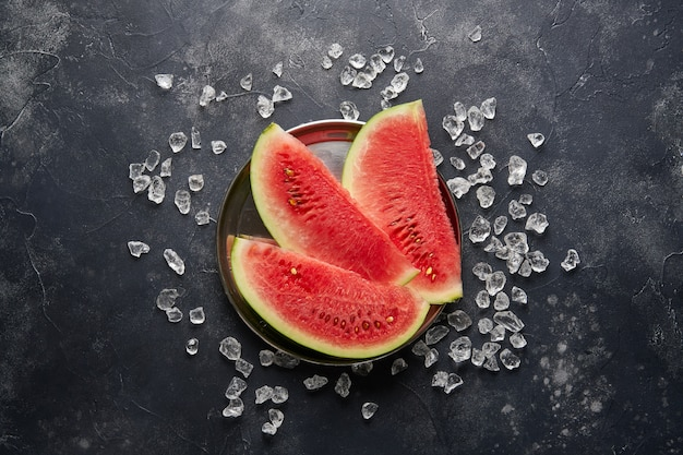 Slices of red watermelon and ice cubes on dark table, top view