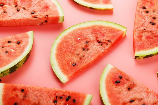 Slices of red watermelon on pink