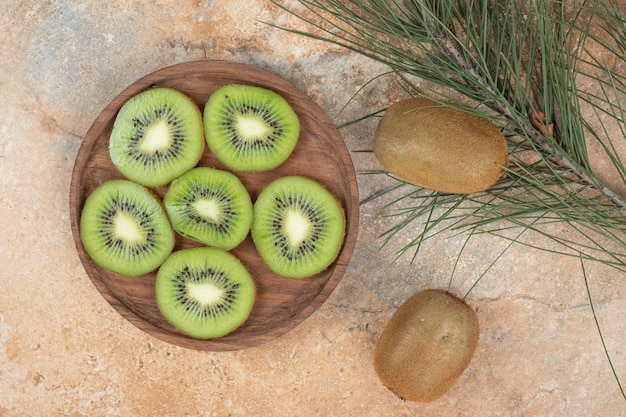 Slices of ripe kiwi on wooden plate.