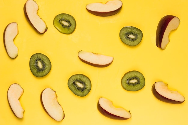 Slices of ripe red apples and juicy kiwi on yellow background
