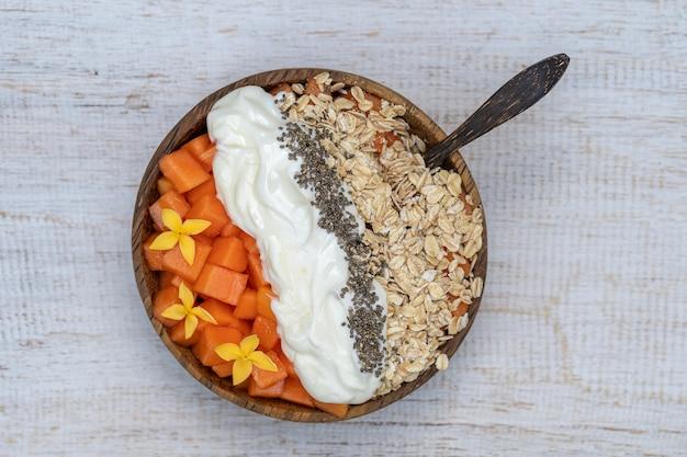 Slices of ripe sweet papaya fruit with oat flakes, chia seeds and white yogurt