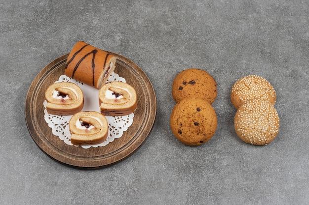 Fette di torta rotolo su tavola di legno con i biscotti