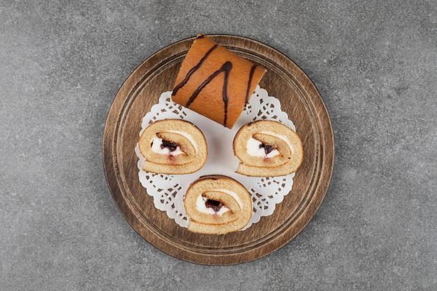 Fette di torta rotolo su tavola di legno