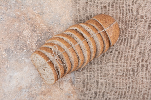 Slices of rye bread on marble surface with burlap