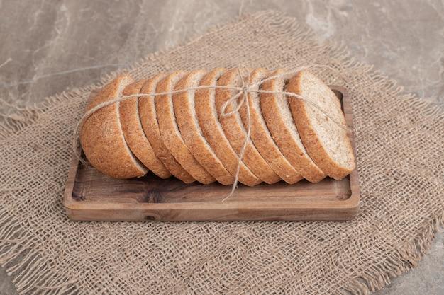 Fette di pane di segale sul piatto di legno con tela. foto di alta qualità