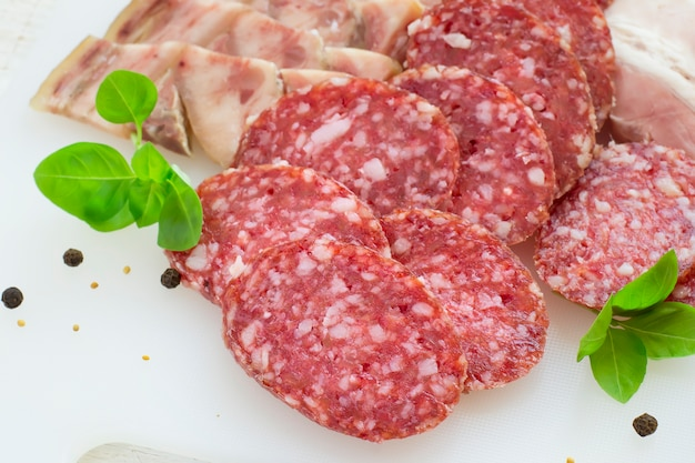 Slices of salami and bacon on a white background