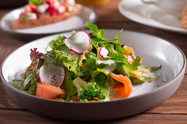 Slices of salmon with fresh vegetable salad on a plate.