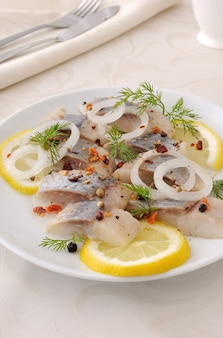 Slices of salted herring fillet with onion, lemon and spices