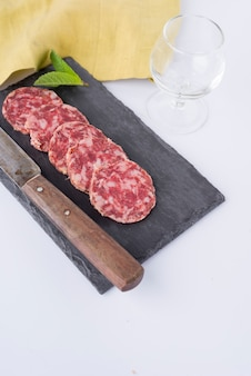 Slices of sausage on slate board, knife, empty glass and yellow cloth