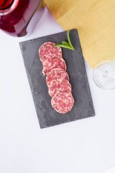 Slices of sausage on slate table, red bottle, empty glass and yellow cloth