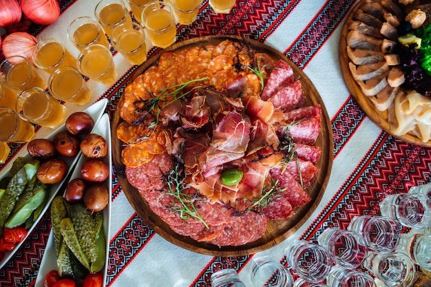 Slices of smoked meat served with greenery lie on the wooden Free Photo