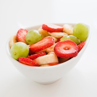 Slices of strawberries; banana; grapes in bowl on white backdrop