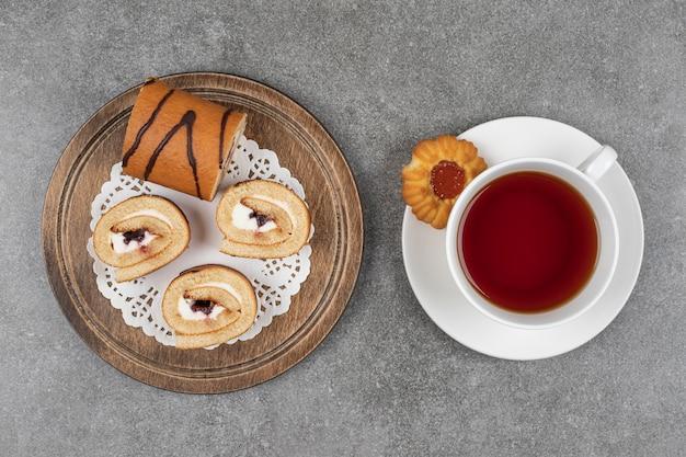 Fette di torta dolce roll sulla tavola di legno con una tazza di tè