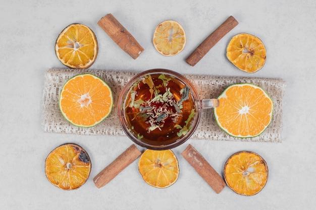 Fette di mandarini e tazza di tè nero sul tavolo di marmo. foto di alta qualità