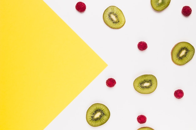 Slices of tasty kiwi and raspberry on multicolored background