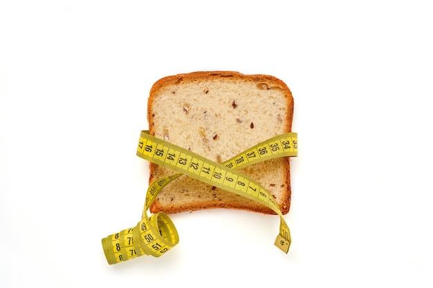 カボチャ、ポピー、亜麻、ヒマワリ、ゴマ、キビを白いテーブルに分離した小麦の穂で飾ったさまざまな種子でトーストパンをスライスします。上面図。