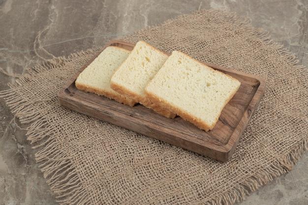 Fette di pane tostato sul piatto di legno. foto di alta qualità