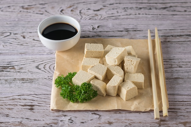Slices of tofu cheese, soy sauce and wooden sticks. soy cheese. vegetarian product.