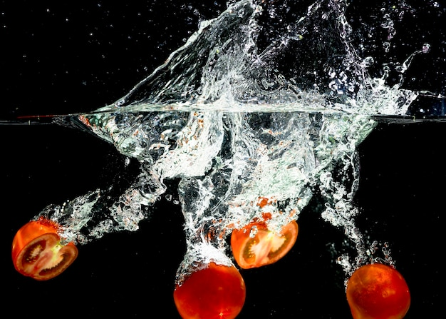 Slices of tomatoes falling into splash of water against black background