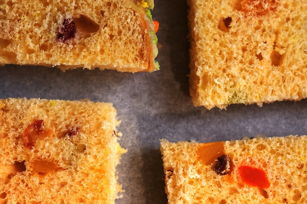 Slices of traditional dried fruits cake for christmas ready for baking on the baking sheet