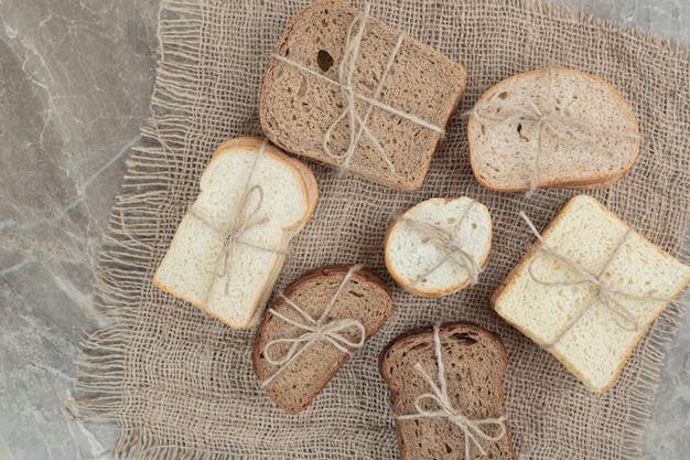 Fette di pane vario legate con una corda sulla superficie in marmo. foto di alta qualità