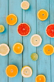 Slices of various juicy citrus fruits on wooden backdrop