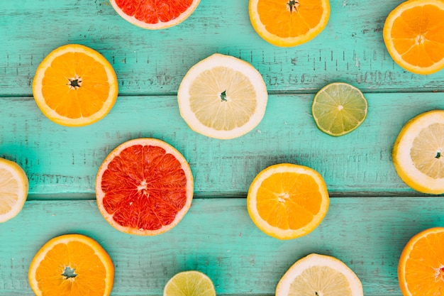 Slices of various juicy citrus fruits on wooden table top