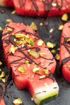 Slices watermelon in ice cream or popsical  shape with chocolate and pistachio nuts decoration, close up