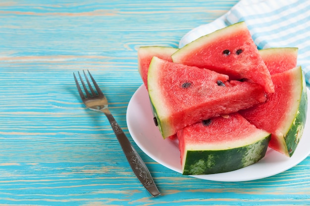 Slices of watermelon on the plate on blue wooden background with fork and checkered towel.