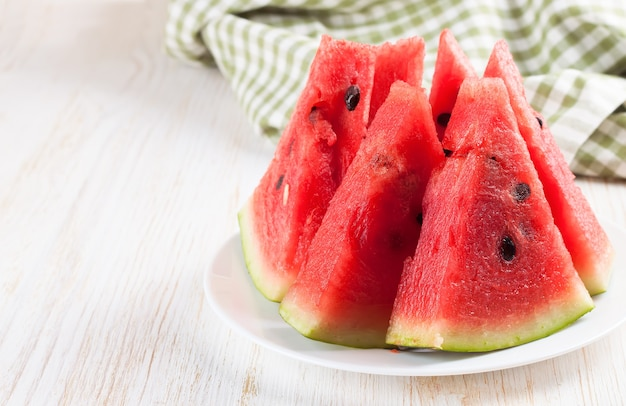 Slices of watermelon on the plate on white wooden background with fork and green checkered towel.