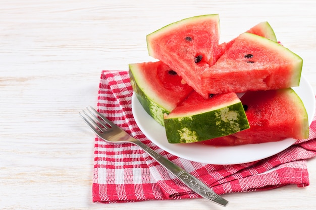 Slices of watermelon on the plate on white wooden background with fork and red checkered towel.