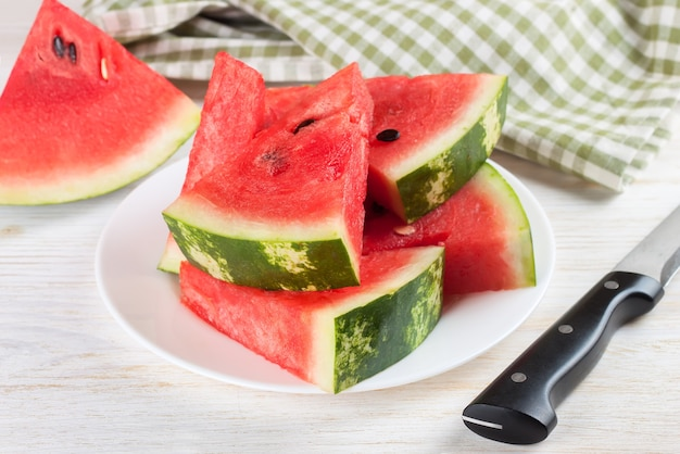 Slices of watermelon on the plate on white wooden background with knife and checkered towel.